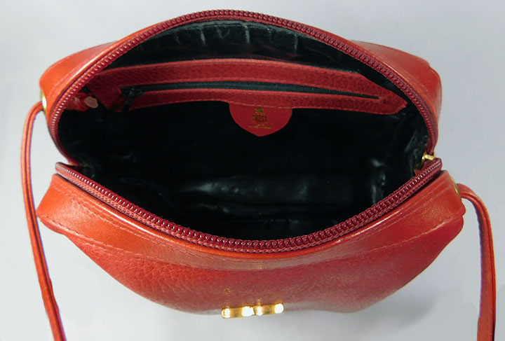 An adorable small vintage red leather shaped duffel handbag by Mark Cross.  The red leather has a pebble texture and the thin 80's style strap is cross  the ...